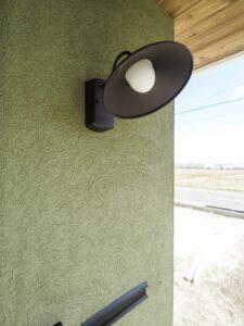 塗り壁と照明がアクセントのポーチ