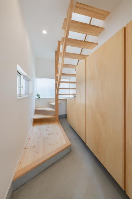 ストリップ階段から光の差し込む玄関