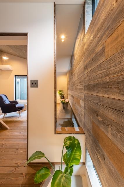 玄関からリビングへ抜ける板張りの壁面