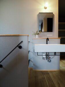 グレーの壁紙と黒のスチール手摺と造作洗面