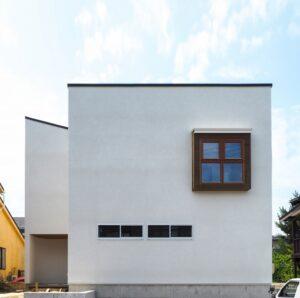 レッドシダーの出窓がアクセントの白い箱の家